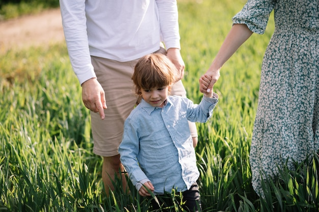 Маленький мальчик 3 лет проводит время с родителями в траве в парке, концепция счастливого детства