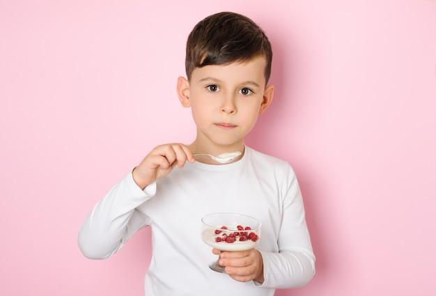 ピンクの表面に赤いベリーとヨーグルトを食べる6歳の少年
