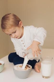 Little boy adding milk to cereals