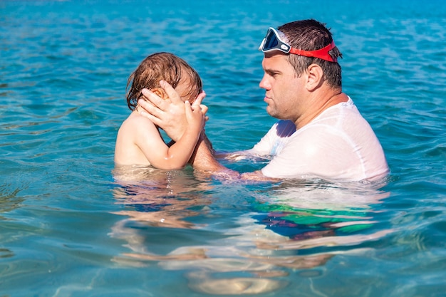 Little boy afraid of water stinging eyes in the sea. father and little son swimming and playing together in sea water at summer holidays