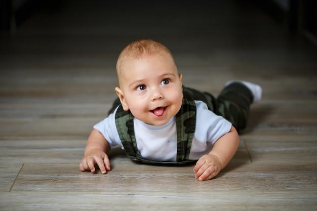 Маленький мальчик 8 месяцев в комбинезоне, белой рубашке и белых носках ползет по полу и улыбается