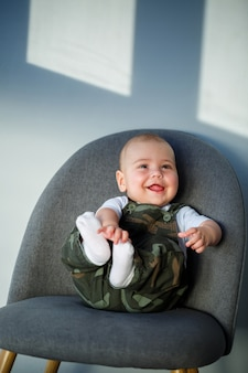 Маленький мальчик 8 месяцев в комбинезоне, белой рубашке и белых носках сидит на сером стуле