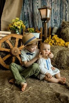 Маленький мальчик и девочка сидят на соломе в пасхальном украшении со стогом сена и утятами. пасха для детей