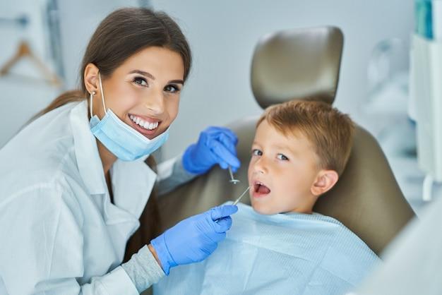 Маленький мальчик и женщина-стоматолог в офисе стоматолога