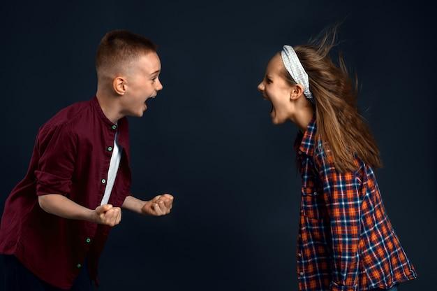 어린 소년과 소녀는 서로에게 소리를 지르며 머리카락 효과를 개발합니다. 어린이와 바람, 어두운 배경에 고립 된 어린이, 어린이 감정