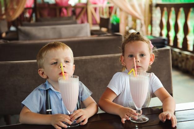男の子と女の子が屋外のカフェでミルクセーキを飲みます。