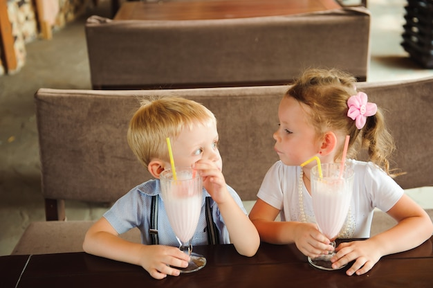男の子と女の子が屋外のカフェでミルクセーキを飲みます。 Premium写真