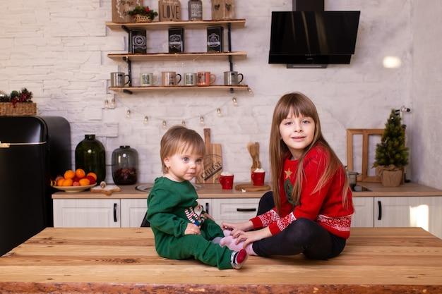 自宅の台所で小さな男の子と女の子が台所のテーブルに座っています