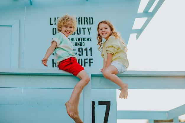 해변의 인명 구조 타워에 앉아 여름 옷을 입은 어린 소년과 소녀