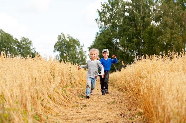 실행, 즐기는 자연 재생 햇빛에 밀밭에 작은 소년과 소녀. 필드와 일몰 하늘 배경 위에 키우는 아이. 어린이 환경 개념