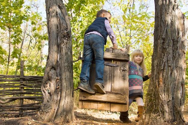 시골 숲에서 야외에서 하루를 즐기면서 두 나무 사이의 오래된 소박한 나무 문에서 노는 어린 소년과 소녀