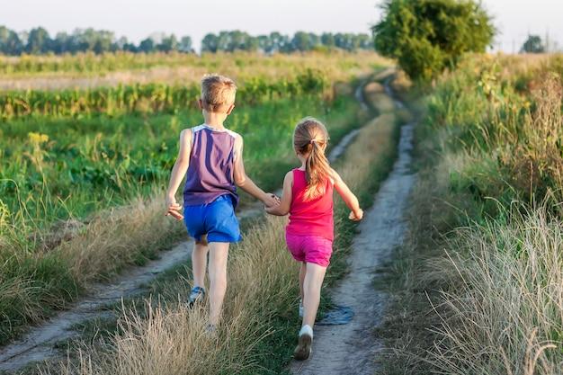 男の子と女の子のフィールド道路で実行されています