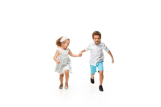 Маленький мальчик и девочка, бегущие на белом фоне, счастливы