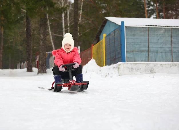 小さな男の子と女の子がそりで雪の丘から滑り降りる