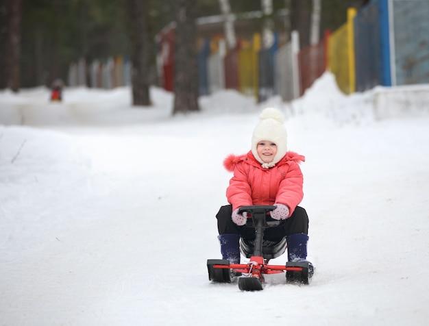 Маленький мальчик и девочка спускаются со снежной горки на санях