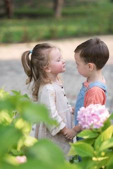 어린 소년과 소녀는 손을 잡고 발렌타인 데이에 키스를 서