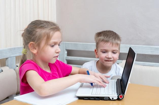 Маленький мальчик и девочка учатся дома онлайн. девушка набирает текст на ноутбуке.