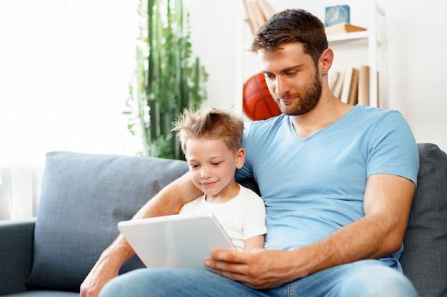 小さな男の子と彼のお父さんは一緒に自宅のソファに座ってデジタルタブレットでビデオを見ています