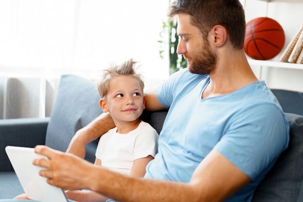 小さな男の子と彼のお父さんは一緒にソファに座ってデジタルタブレットでビデオを見ています