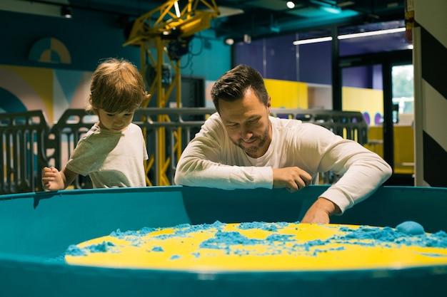 어린 소년과 그의 아버지는 어린이 발달 센터에서 운동 모래를 가지고 놀고 있습니다. 가족 관계. 부모의 사랑과 지원. 어린이 발달 센터. 현대 레저.