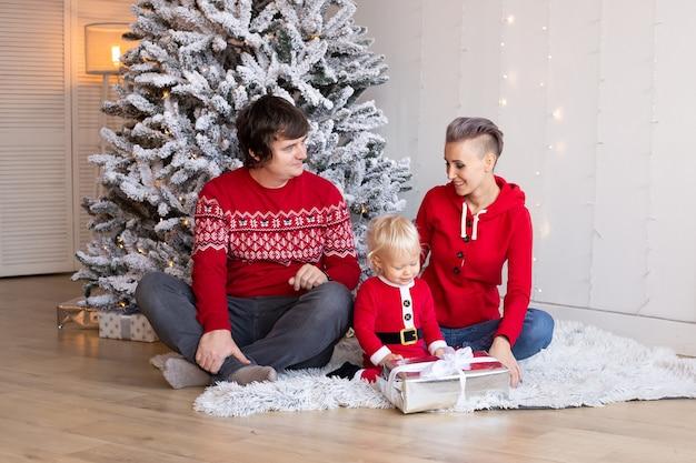小さな男の子と彼の幸せな両親は、背景にクリスマスツリーを持って家にいます。クリスマスツリーの近くで遊んで幸せな少年。