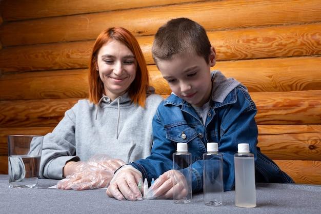 어린 소년과 그의 어머니는 다양한 화학 원소가 담긴 시험관과 항아리를 배치하고 있습니다.
