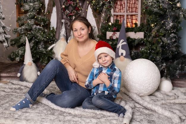 Маленький мальчик и его мать возле елки, игрушечного домика и гномов. волшебное праздничное украшение для дома