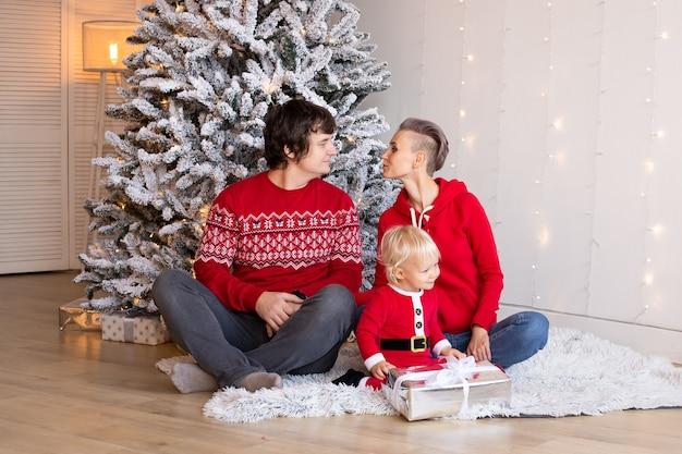 小さな男の子と彼の両親は、背景にクリスマスツリーを持って家にいます。クリスマスツリーの近くで遊んで幸せな少年。