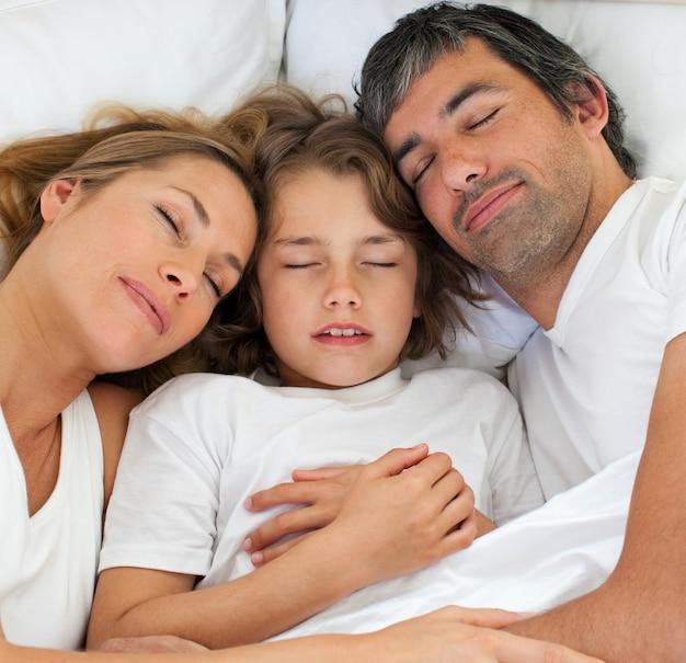 小さな男の子と両親が一緒に寝る