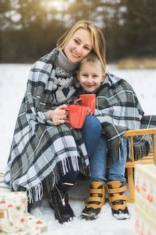 Маленький мальчик и мать, скольжение в зимнем лесу. мама и сын сидят на санях