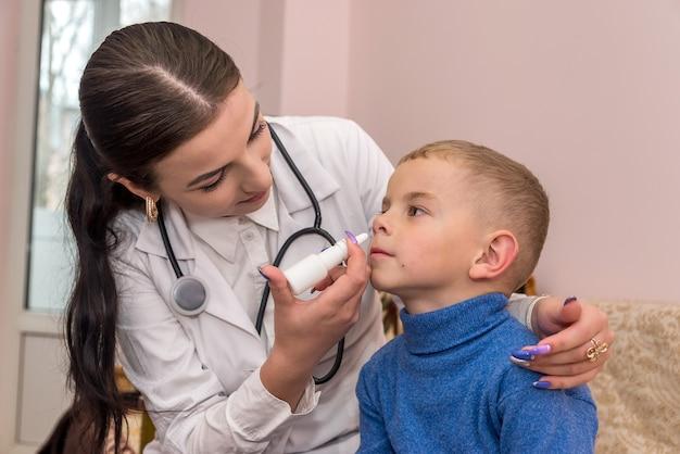 小さな男の子と小児科医が彼の鼻を滴らせます