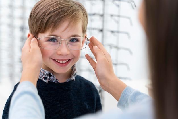 Маленький мальчик и сестра в магазине примеряют очки