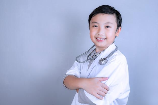 コピースペースのある医者の制服を着た小さな男の子と聴診器。