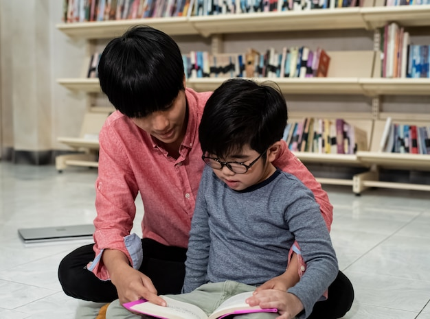 小さな男の子と先生が一緒に本を読んで、周りのぼやけた光