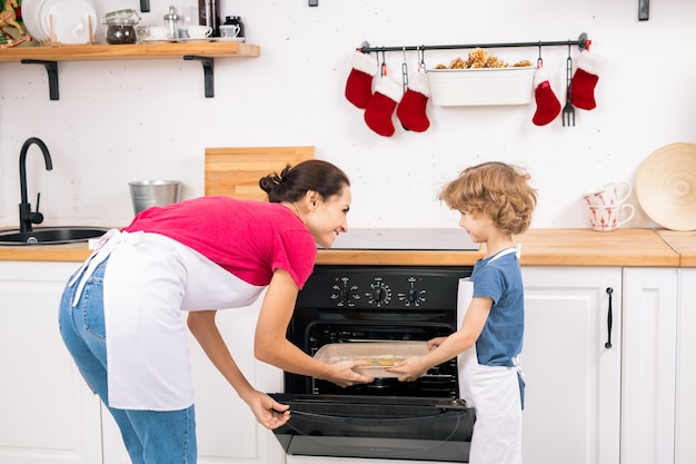 Little boy in apron helping his mom put tray with raw cookies into open oven while both looking at each other