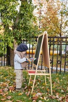 Little boy artist draws paints on canvas easel