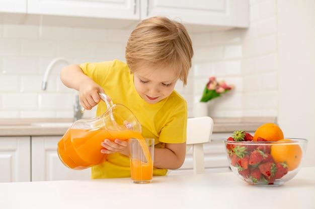 Маленький мальчик дома наливает сок