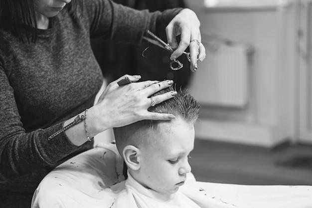 Маленький мальчик в парикмахерской. ребенок боится стрижки. руки парикмахера делают прическу маленькому мальчику, крупным планом. модная стрижка для мальчиков.
