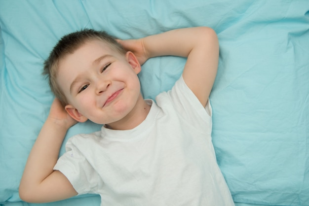 Little boy awakes in his bed and smiles