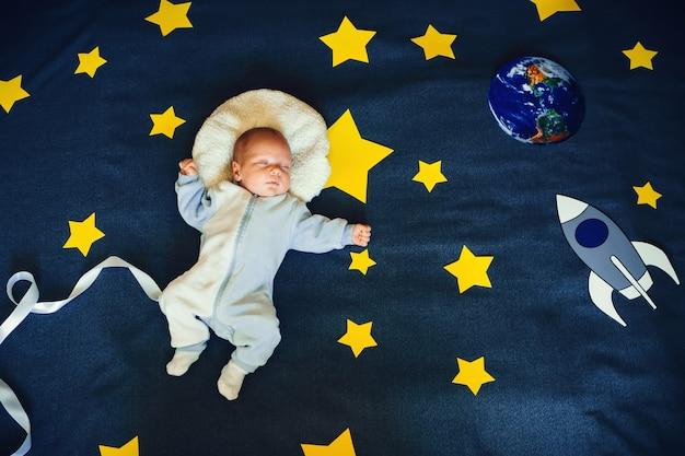 별이 빛나는 하늘의 우주 비행사의 소송에서 자고있는 어린 소년 아기
