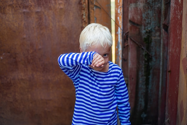 Little boy on the background of a rusty door wipes tears with his hands.