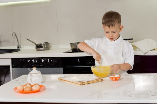 Little boy baking beating a mixture of flour and eggs in a mixing bowl at a kitchen table