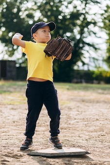 Little boy in a baseball cap, gloves throws a baseball
