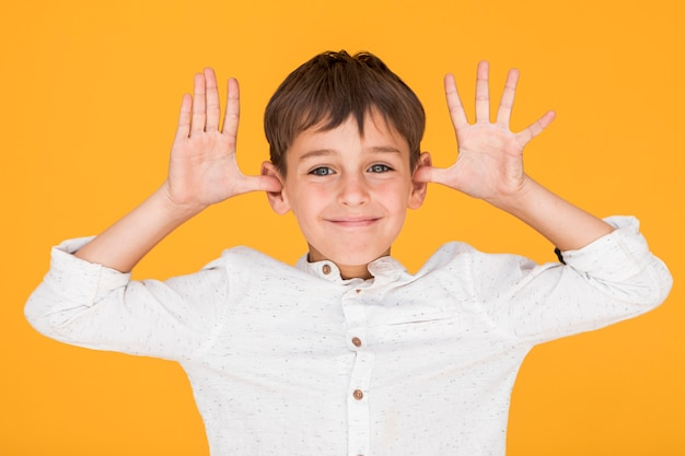 Little boy being silly with orange background