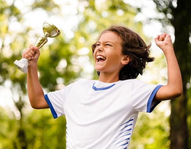 Маленький мальчик побеждает после футбольного матча