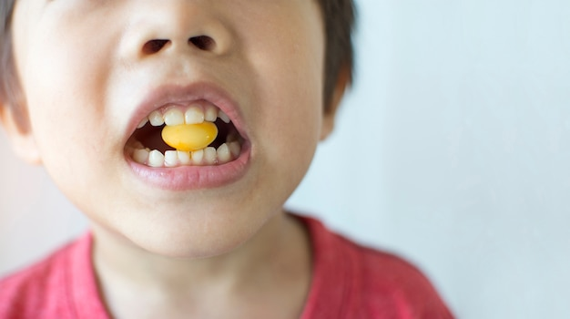 Little boy biting yellow candy in a mouth with copy space.