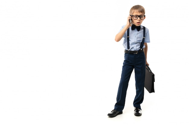 Little boy in black glasses with transparent glasses, blue shirt, pull-ups, blue pants, black case talks on the phone
