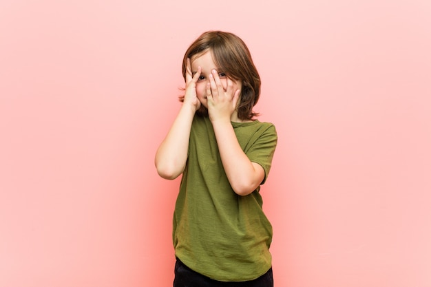 Маленький мальчик моргает сквозь пальцы испуганно и нервно.