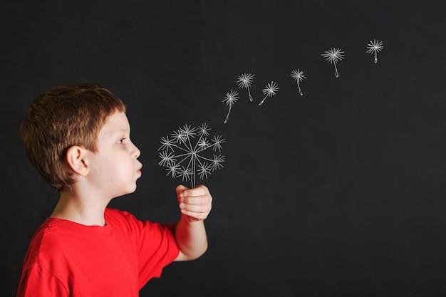 Little boy blowing dandelion with drawing in blackboard.