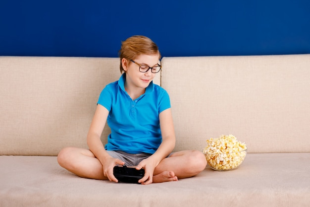 A little boy in blue t-shirt and big glasses sitting on the couch and playing with a gamepad while eating popcorn
